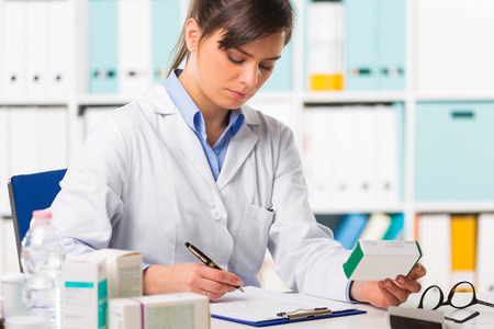 Pretty young female pharmacist in white coat sat at desk writing notes with boxes of medicine in foreground