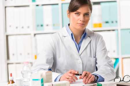 earnest: Half body portrait of attarctive young female pharmacist in white coat sat at desk writing notes with boxes of medicine in foreground