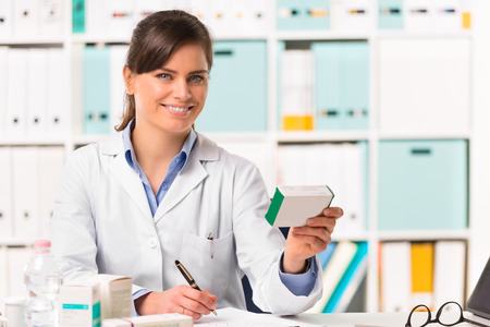 Half body portrait of Smiling young female pharmacist in white coat sat at desk writing notes with boxes of medicine in foreground