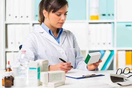 Pretty young smiling female doctor sat at desk writing notes with boxes of medicine in foreground Stock Photo