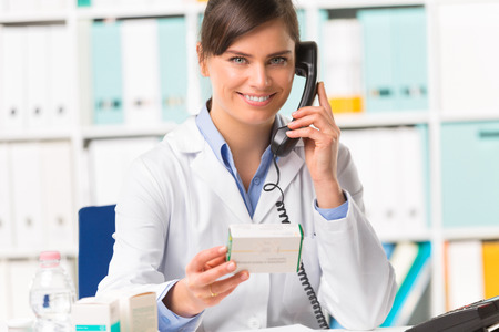 Smiling Young female pharmacist in white coat on phone holding medicine packet in hand