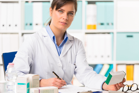Half body portrait of attarctive young female pharmacist in white coat sat at desk writing notes with boxes of medicine in foreground