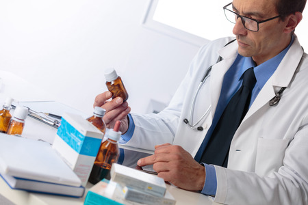 Portrait of Adult male pharmacist in white coat sat at desk reading notes with boxes of medicine in foreground Stock Photo