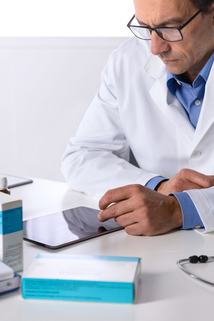 dispensary: Portrait of Thoughtful Adult male doctor with stethoscope at desk using tablet