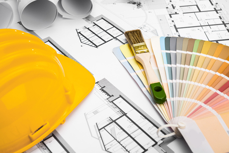 brush painting: Construction plans with Paint Brush Colors Palette and Yellow Safety Helmet on blueprints; Building and Construction Industry Concept Stock Photo