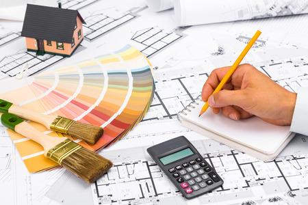 電卓を使用して、ノートに書いてアカウントに取り組んでの実業家。青写真; カラー パレットとミニチュアの家建設計画ビジネスと建設産業のコンセプト