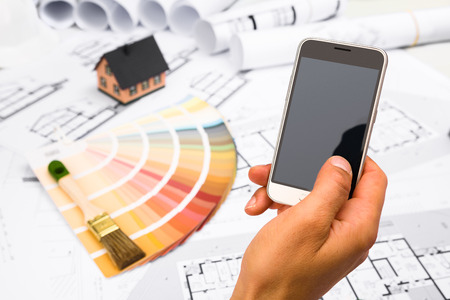 communication industry: Male Hand holding a Smart Phone; Construction plans with Color Palette and Miniature House on blueprints Background; Communication and Construction Industry Concept Stock Photo