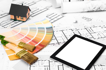 communication industry: Construction plans with Color Palette Miniature House and white Screen Tablet on blueprints Background; Communication and Construction Industry Concept
