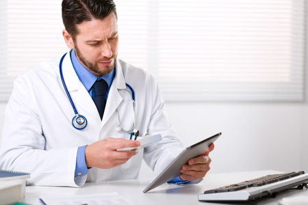 Male doctor holding tablet and the box of medicine, sitting at white table, looking at screen