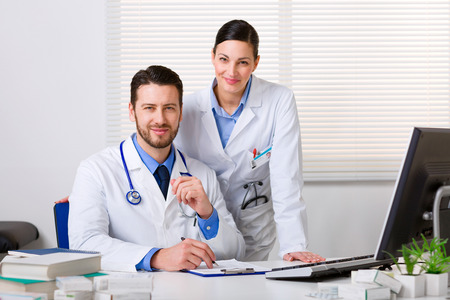 Two smiling young doctors in white coat working in an office and looking at camera
