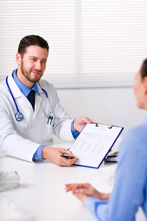 requesting: Doctor requesting the signature of a female patient on paperwork holding out the clipboard to her with a pen Stock Photo