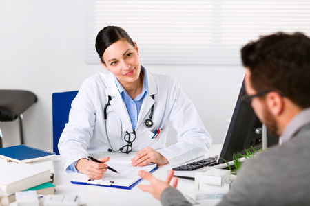 Young female doctor listening intently to a male patient explaining his symptoms or asking a question as they discuss paperwork together in a consultation