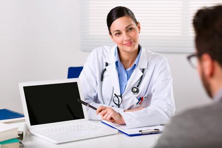 그는 자신의 증상을 설명하는 상담을하는 동안 남성 환자에게 열심히 듣고 여성 의사 스톡 콘텐츠