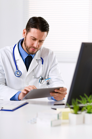finding the cure: Male doctor with stethoscope on his neck using tablet, looking at screen and sitting at white table Stock Photo