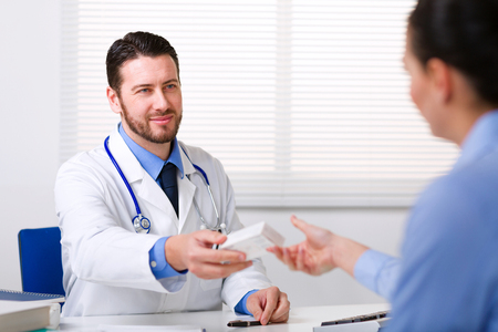 by pass surgery: Male doctor smiling and passing box of medicine to patient over table