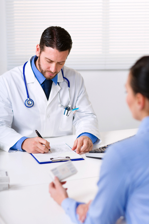 Young male doctor sitting at table in front of patient or nurse and writing prescription while woman holding box of medicine blurred in foreground