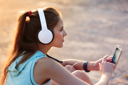 auriculares: Mujer sonriente joven con la ropa deportiva escuchando música con auriculares desde su teléfono inteligente en el parque durante la puesta del sol