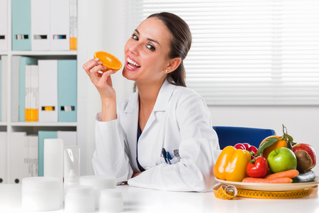dietetics: Smiling Female nutritionist eating an Orange Slice in her office and showing healthy vegetables and fruits; Healthcare and diet concept