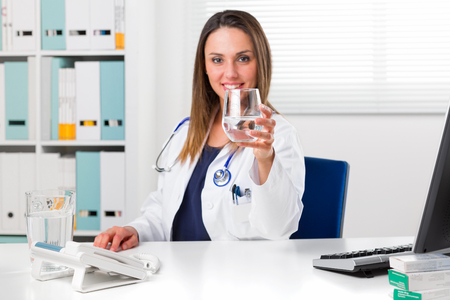 Portrait of Smiling Female Doctor offering a glass of water in her Office; Detox and Cleansing concept