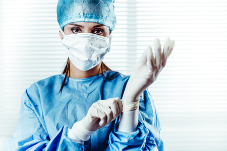 Portrait of Female doctor Surgeon in blue scrubs putting on surgical gloves and Looking at Camera Standard-Bild