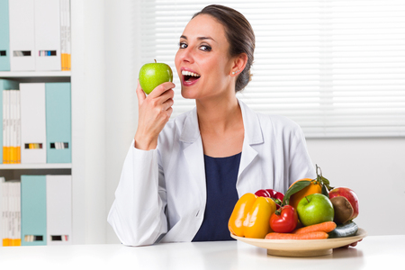 Smiling Female nutritionist eating a Green Apple in her office and showing healthy vegetables and fruits; Healthcare and diet concept