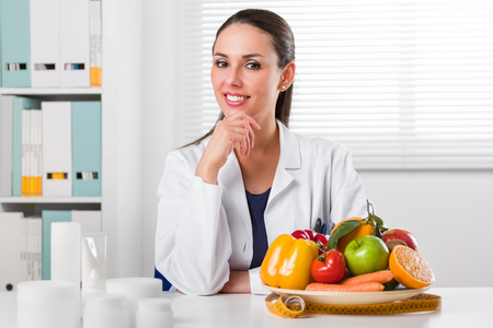 dietetics: Smiling young Female Dietitian sitting at desk and showing colorful vegetables and fruit, healthy eating and diet concept