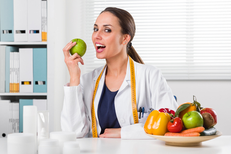 Smiling Female nutritionist with tape measure around her neck eating a Green Apple in her office and showing healthy vegetables and fruits; Healthcare and diet concept Stock Photo