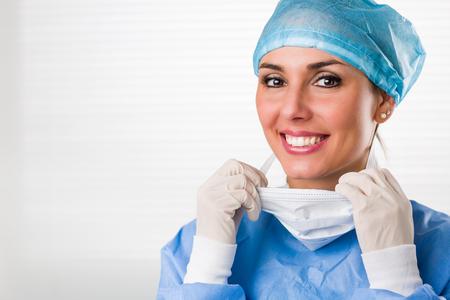 Portrait de belle chirurgien féminin souriant portant des gants de masque de casquette et des gommages bleus. Fond blanc