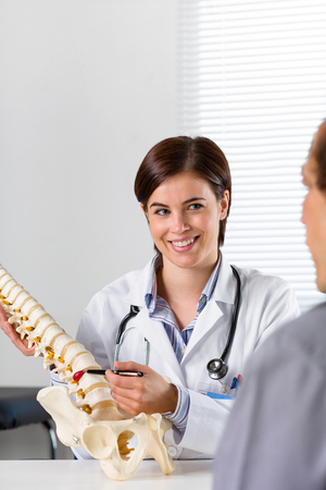 Female Orthopaedic surgeon explaining a back injury or disease to a male patient on crutches with the help of a human spine Stock Photo