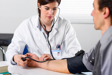 Portrait Of A Female Doctor Checking Blood Pressure Of Male Senior Patient Stock Photo