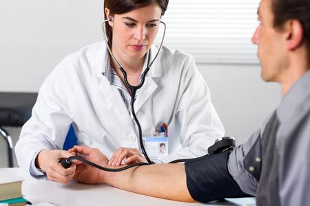 Portret van een Vrouwelijke Arts die Bloeddruk van Mannelijke Hogere Patiënt controleert
