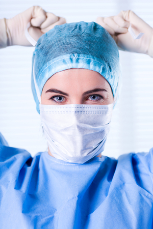 Portrait of Smiling Female Surgeon wearing blue protective uniform, cap and mask