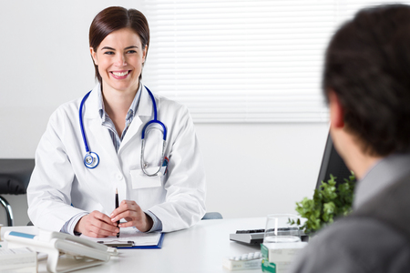 Smiling Young female doctor listening to a male patient explaining his symptoms or asking a question as they discuss paperwork together in a consultation