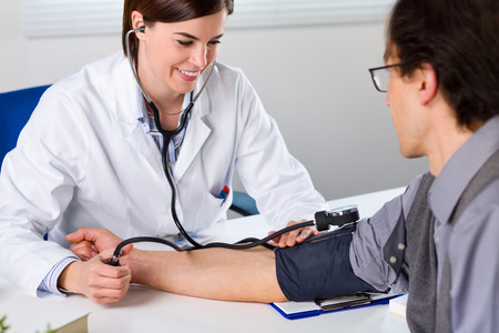 Portrait Of A Smiling Female Doctor Checking Blood Pressure Of Male Senior Patient