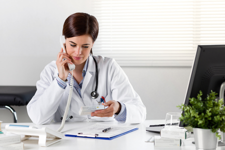 Smiling Young female doctor or pharmacist in white coat on phone holding medicine packet in hand