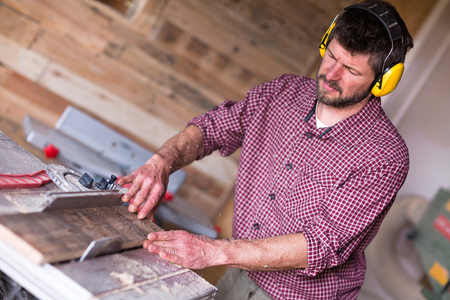 Male Carpenter with ear protector cutting plank by circular saw in his workshop