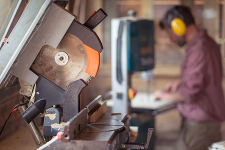 workroom: Circular Saw with Male Carpenter cutting plank by band saw on background; Focus on Circular Saw; Stock Photo
