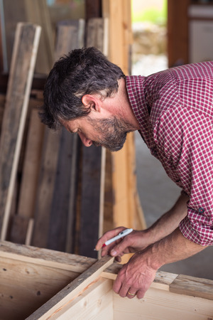 Portrait of Male Carpenter working on wooden furniture in his workshop