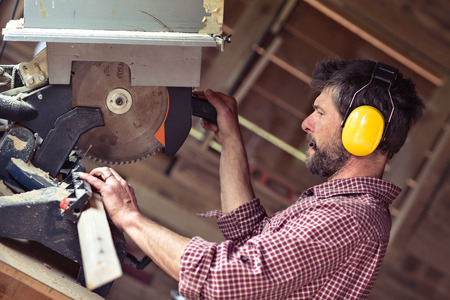 workroom: Male Carpenter with ear protector cutting plank by circular saw in his workshop