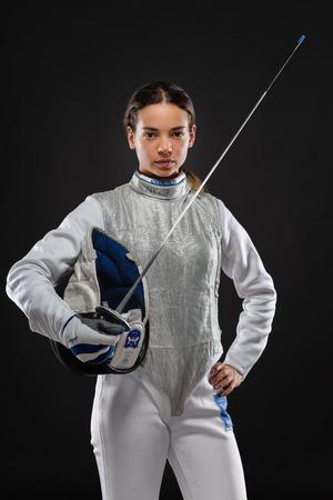 Ritratto dello schermitore della giovane donna che porta il costume di recinzione bianco e che tiene spada e maschera. Guardando la fotocamera Sfondo nero Archivio Fotografico - 84924531
