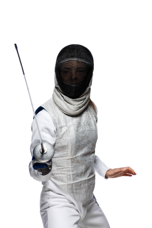 Portrait of Young woman fencer wearing mask and white fencing costume. Attacking pose. Isolated on White Background Imagens