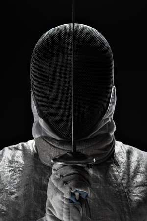 Portrait of Young Male fencer wearing mask and white fencing costume and holding the sword in front of his. Black Background