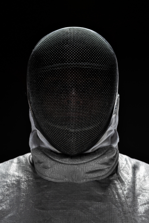 Portrait of Male fencer wearing mask and white fencing costume.  Black Background