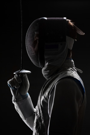 rapier: Profile of Young male fencer wearing white fencing Mask and costume holding the sword in front of his. Black Background