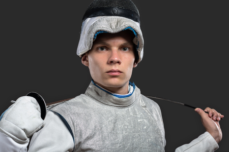 Portrait of Handsome Young male fencer wearing white fencing costume and holding the sword on his shoulders. Dark Background; Looking at camera Stock Photo