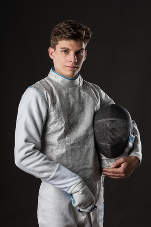 Portrait of Smiling Young male fencer wearing white fencing costume against Dark Background