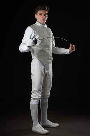 Portrait of Handsome Young male fencer in white fencing costume against Dark Background
