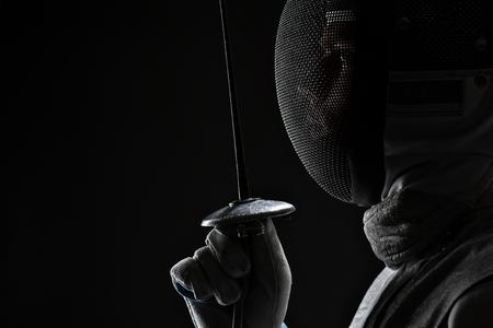 Profil de Jeune homme escrimeur portant une escrime blanche Masque et costume tenant l'épée devant son. Fond noir