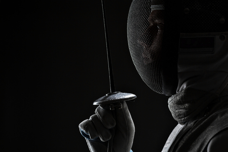 Profile of Young male fencer wearing white fencing Mask and costume holding the sword in front of his. Black Background