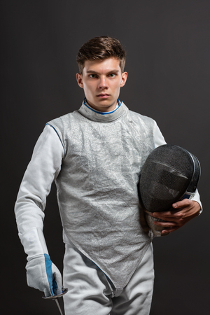 rapier: Portrait of Handsome Young male fencer wearing white fencing costume against Dark Background